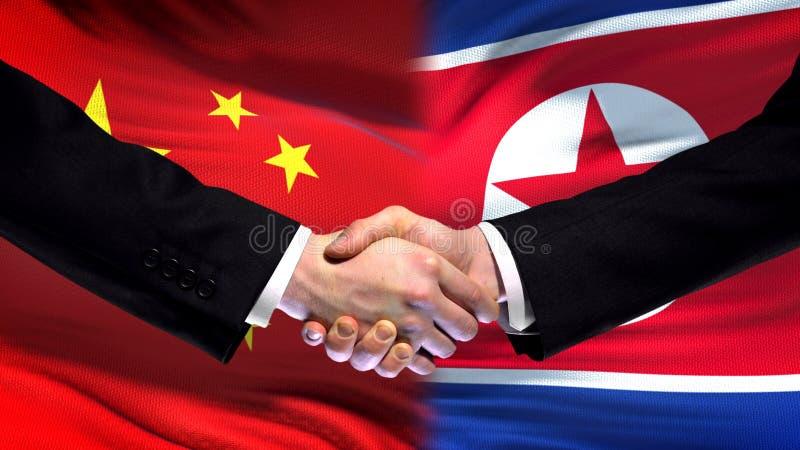 Toppmöte för kamratskap för Kina och Nordkorea handskakning internationell, flaggabakgrund fotografering för bildbyråer