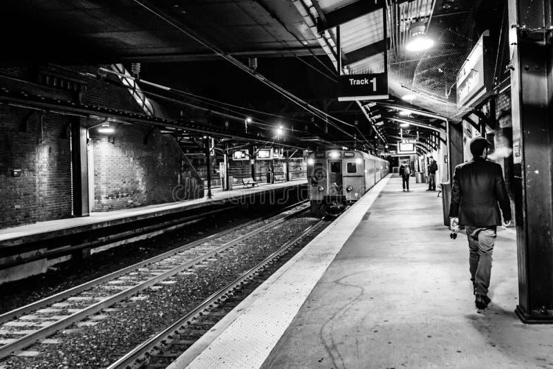 Toppmöte NJ USA - November 1, 2017: En höft- och innegrejman i hatt och sportlag finns stationen för NJ-transportdrevet på natten royaltyfria foton
