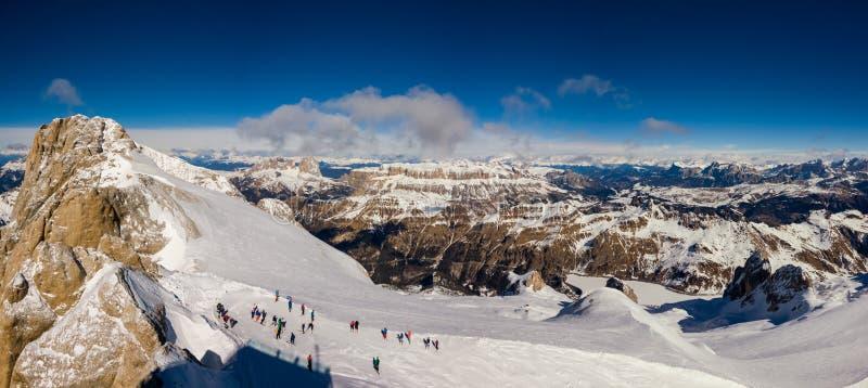 Toppmötet av Marmolada med skidåkare som får klara, och monteringen Sella på bakgrunden på en härlig solig dag, Dolomites, Italie royaltyfri bild