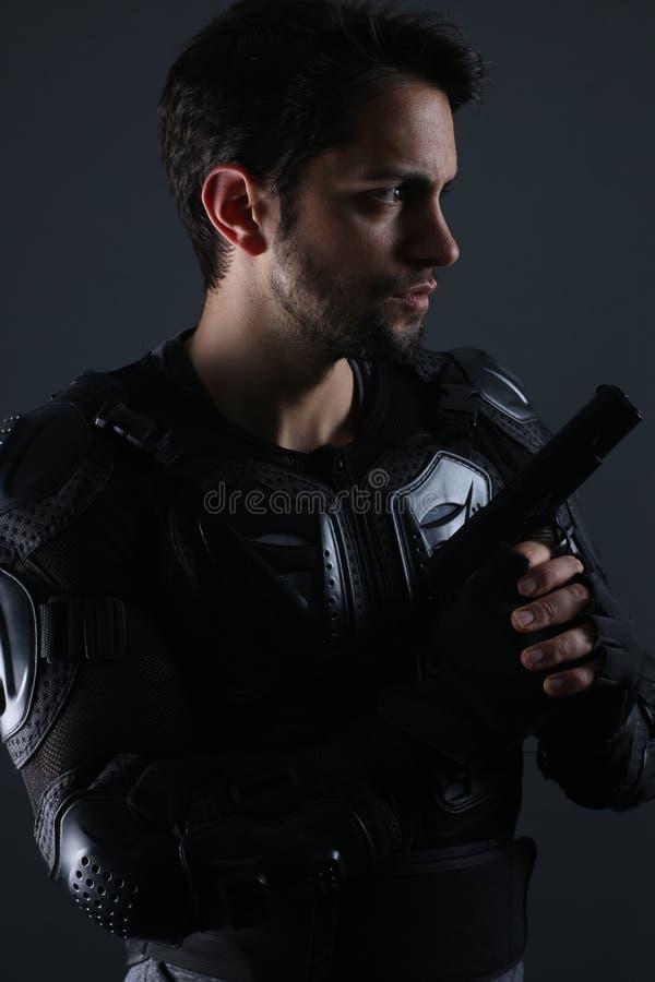 Toppna snutar - stilig mörk haired man som rymmer ett vapen royaltyfri foto