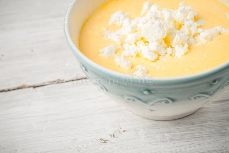 Toppning av ägg, ny ost och yoghurten i den keramiska bunken royaltyfria bilder