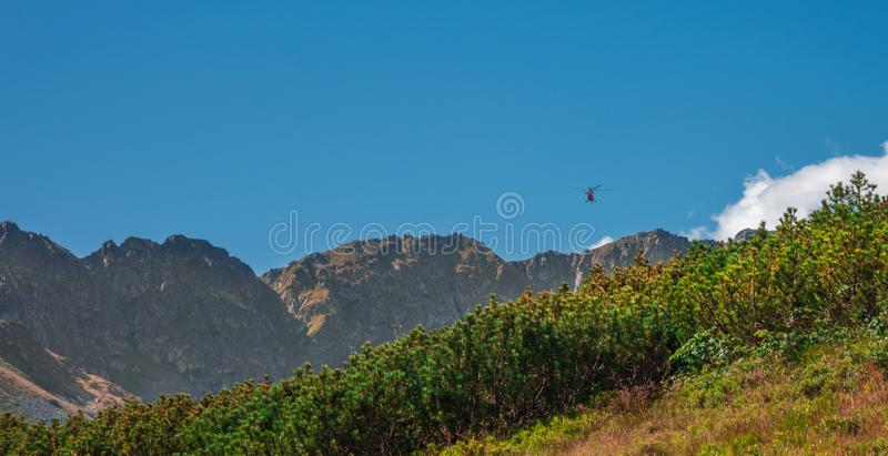 TOPR mountain rescue helicopter heading towards rocky summits to help tourists injured during climbing stock image