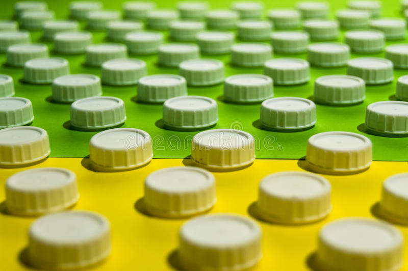 Tops de la botella en superficie verde y amarilla fotos de archivo libres de regalías