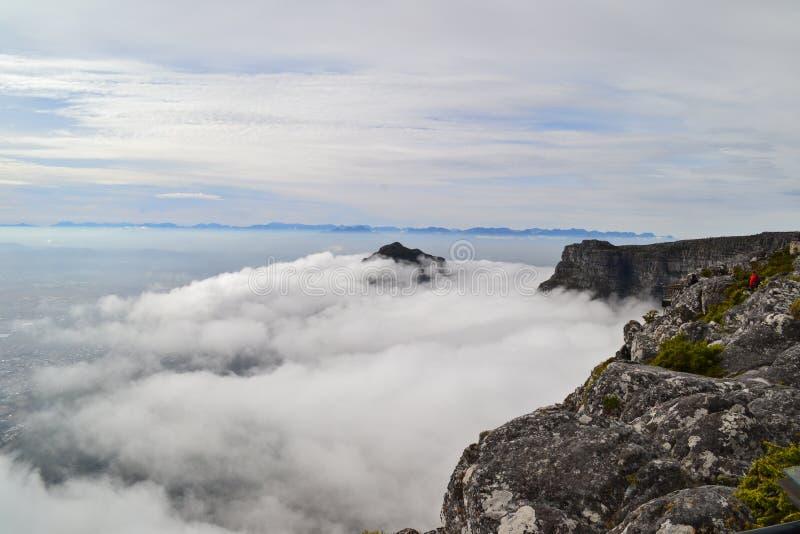 Tops de la montaña que miran a escondidas a través de las nubes brumosas foto de archivo libre de regalías