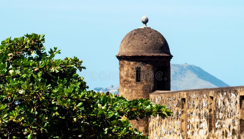 The tops of a fort and a big tree. In the Dominican sunlight, Puerto Plata stock photography