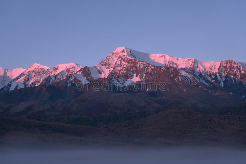 Tops of mountains sparkling by rising sun. Altai region, Siberia, Russia royalty free stock photos