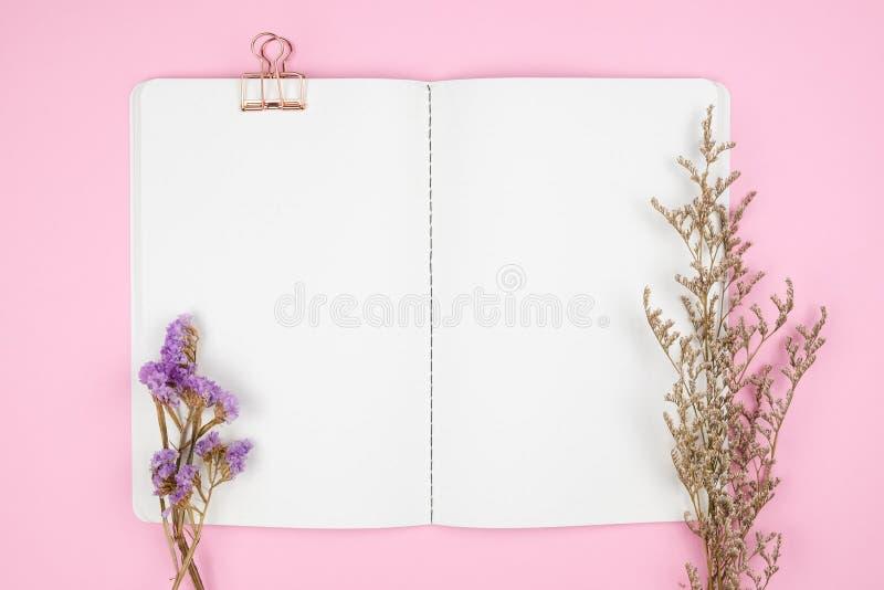 Topsicht auf Schreibwaren und Blumen auf rosa Untergrund stockbilder