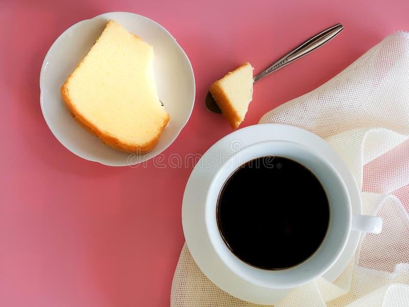 Topview biała filiżanka czarna kawa słuzyć z plasterka masła tortem na naczyniu z różowym tłem zdjęcia royalty free
