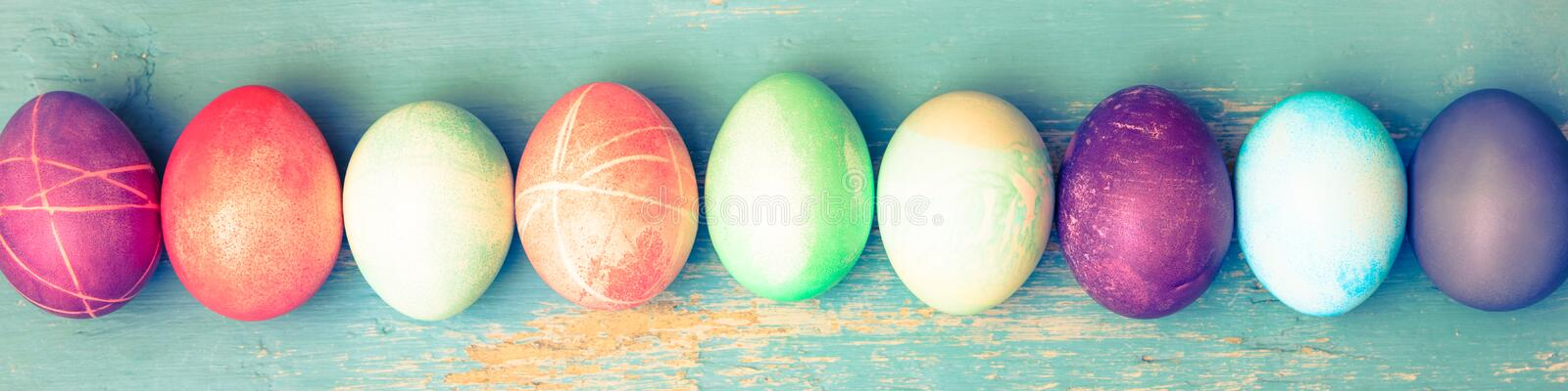 Topview, colorful dyed easter eggs on blue vintage wooden table stock photo