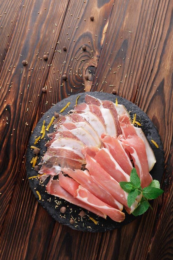 Topview d'un plat de prosciutto légèrement coupé en tranches avec les feuilles vertes fraîches de la menthe sur un fond brun en b image libre de droits