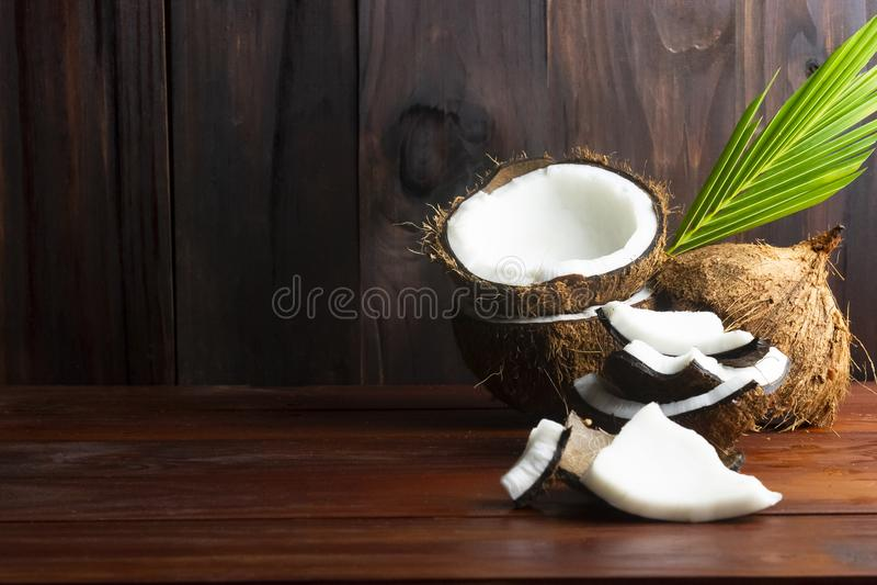 Topview de noix de coco tel que la moitié de noix de coco et les morceaux et la feuille de noix de coco sur la table en bois image libre de droits