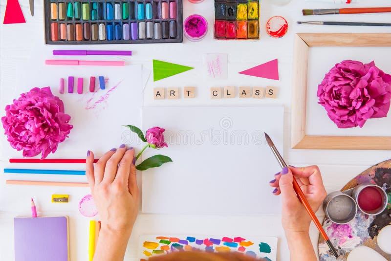 Topview kvinnliga händer som rymmer borsten över tom kanfas med bokstäver för konstgrupp och målar material, pionblommor på vit arkivbild