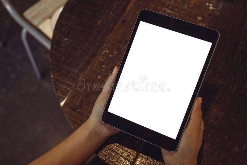 Topview wizerunek ręki trzyma czarnego pastylka komputer osobistego z pustym białym desktop ekranem na drewnianym stole obrazy royalty free