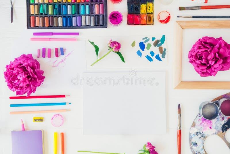 Topviewwerkplaats van creatief kunstenaarsmodel Leeg canvas met tekeningsmaterialen en pioenbloemen op witte achtergrond Workshop royalty-vrije stock foto