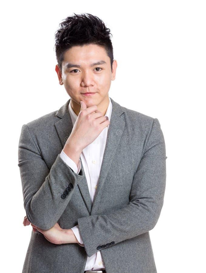 Toque asiático da mão do homem de negócios sua cara foto de stock