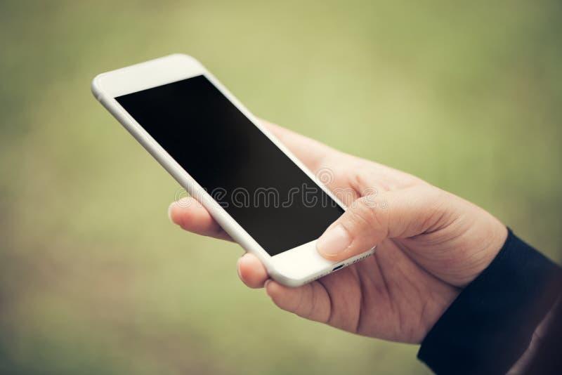 Toque da mão do close-up no conceito exterior do estilo de vida da tela preta vazia móvel do telefone no fundo obscuro da naturez foto de stock