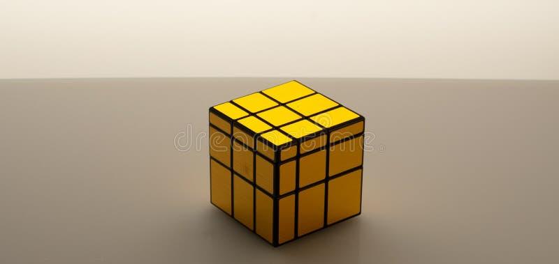 Toque de Cubo Brilhante Ouro sobre fundo cinza fotos de stock