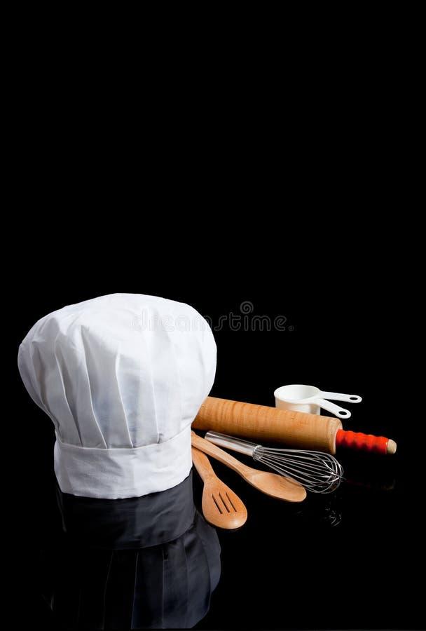 Toque de um cozinheiro chefe com os utensílios da cozinha no preto imagens de stock royalty free