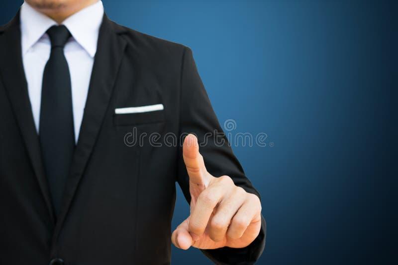 Toque do homem de negócios na tela vitual no fundo azul Isto tem o trajeto de grampeamento foto de stock