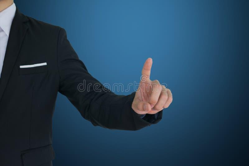 Toque do homem de negócios na tela vitual no fundo azul Isto tem o trajeto de grampeamento imagem de stock