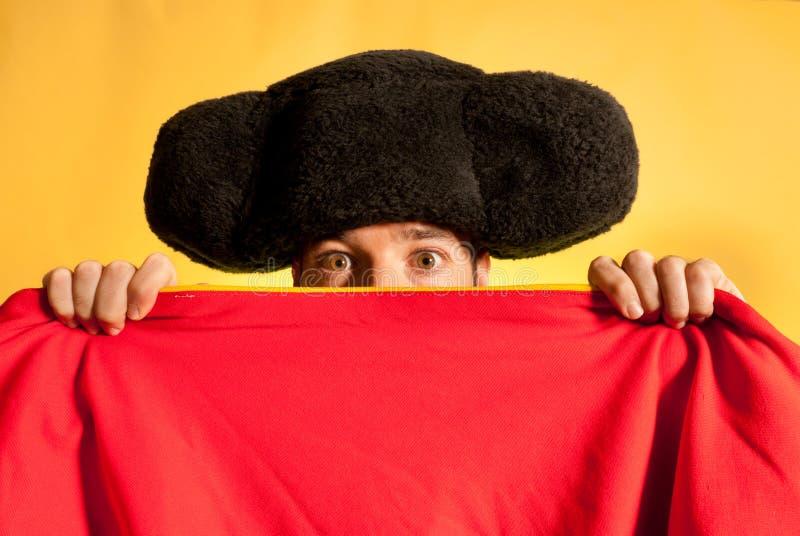Toréador effrayé avec le grand chapeau caché derrière le cap photo stock