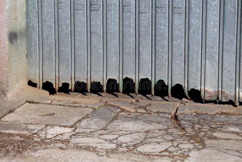 Tor der ruinierten Garage gegen Wetterelemente lizenzfreie stockfotografie
