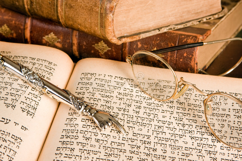 Torah pointer and glasses. Silver Torah pointer lying on a jewish prayer book royalty free stock image