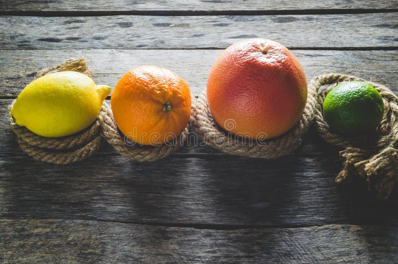 Toranja e cal alaranjados do limão dos citrinos no fundo de madeira velho foto de stock