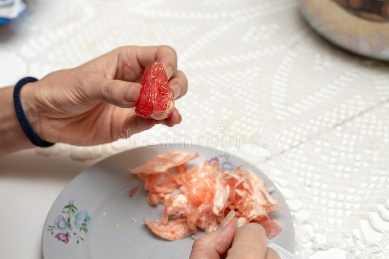 Toranja saboroso preparada para comer As mãos e as citrinas das mulheres fotos de stock royalty free