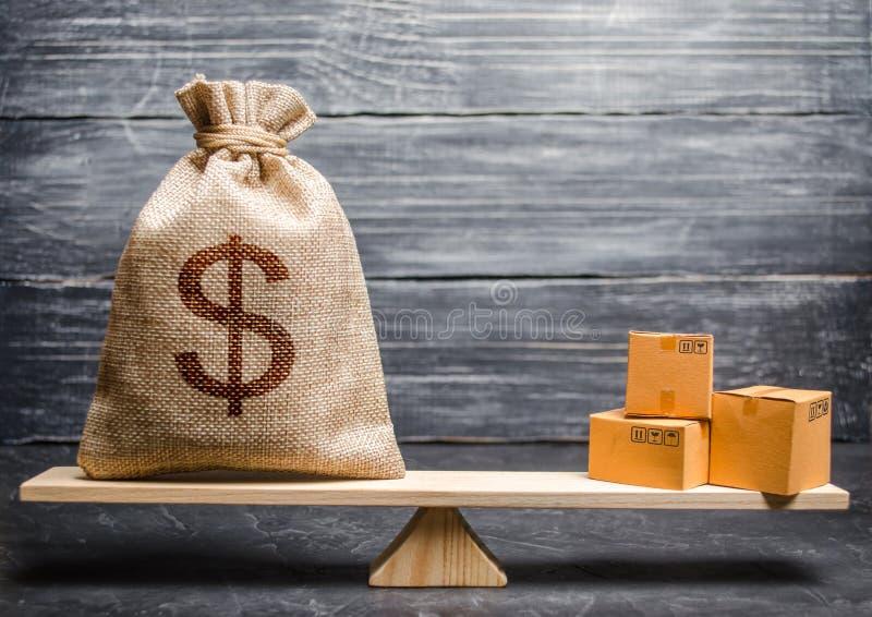 Torba pieniądze i wiązka pudełka na skalach Konceptualny bilans handlowy między krajami, zjednoczenia, handel i wymiana, zdjęcie stock