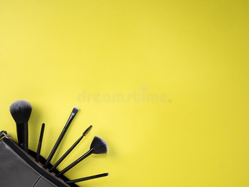Torba z makeup szczotkuje, kosmetyki, żółty tło zdjęcia stock