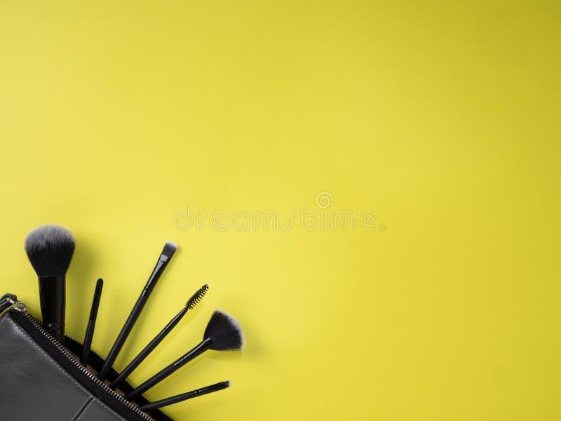 Torba z makeup szczotkuje, kosmetyki, żółty tło obraz royalty free