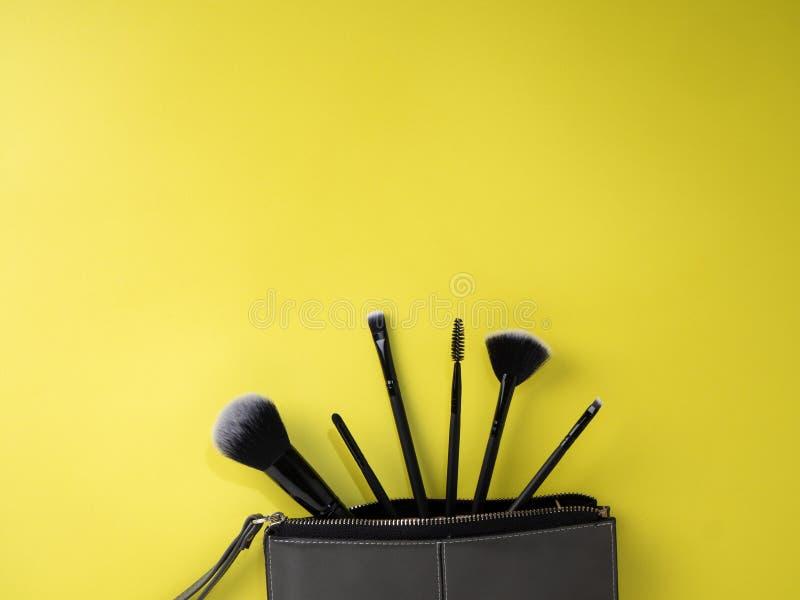 Torba z makeup szczotkuje, kosmetyki, żółty tło obraz stock