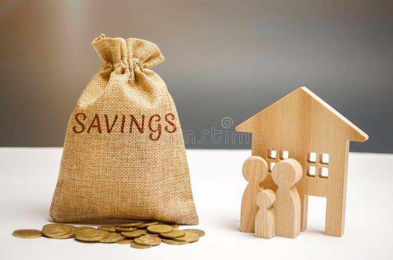 Torba z pieniądze słów oszczędzania i drewniany dom Pojęcie nieruchomość zakup Kupuje dom, mieszkanie proroctwo obraz stock
