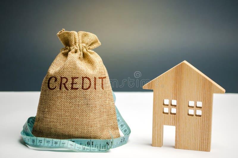 Torba z pieniądze, taśmy miara słowo kredyt i drewniany dom Brak pieniądze płacić pożyczkę Hipoteka dla mieścić obraz stock