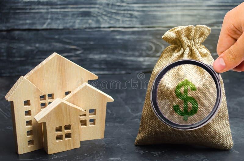 Torba z pieni?dze i drewnianymi domami domowy sprzedawanie Mieszkanie zakup Rynek Nieruchomo?ci Do wynaj?cia budynek mieszkalny d zdjęcie stock