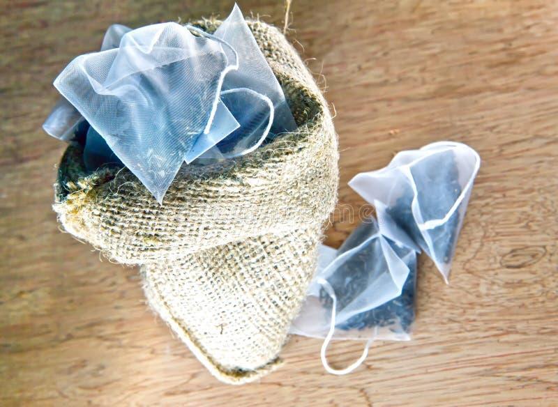 Torby elita herbata w jedwabniczej tkaniny kocowaniu na drewnianym tle mała głębia ciętość zdjęcie stock