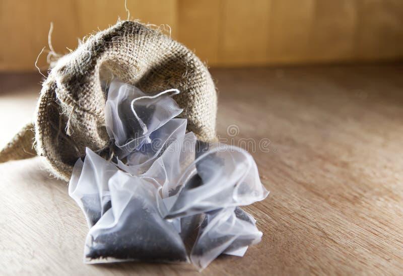 Torby elita herbata w jedwabniczej tkaniny kocowaniu na drewnianym tle mała głębia ciętość zdjęcie royalty free