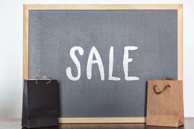 Torby na zakupy i blackboard z słowo sprzedażą Sprzedaż, rabat, sezon sprzedaży pojęcie obraz stock