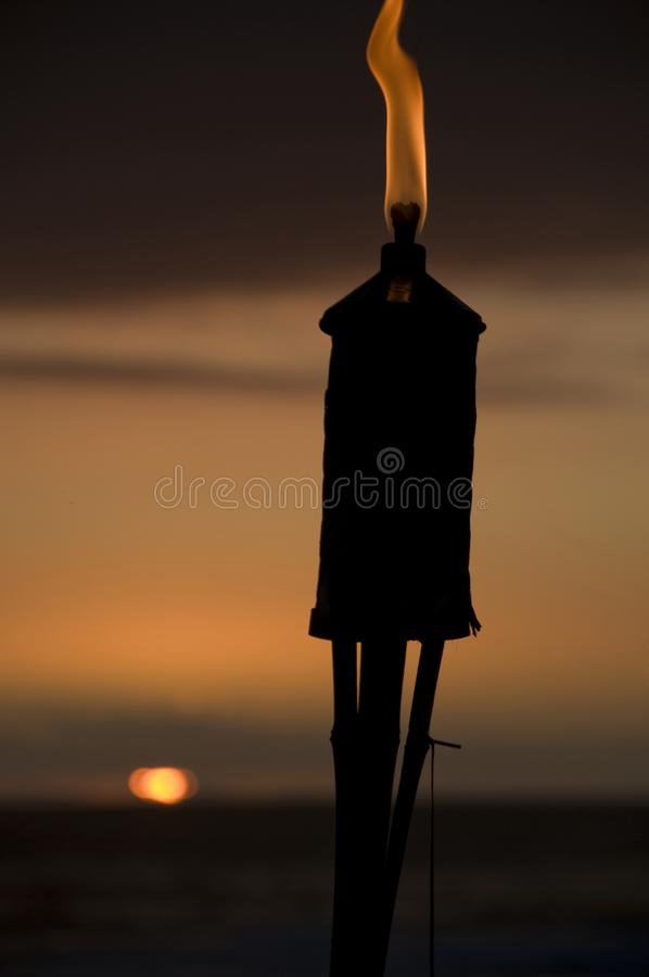 Torch on the beach at sunset. royalty free stock image