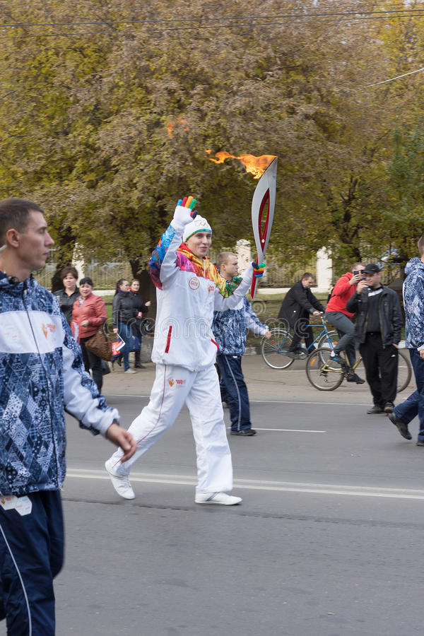 Torchbearer Carries The Olympic Flame Editorial Photo