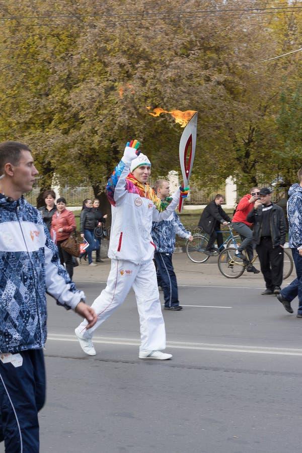Torchbearer trägt die olympische Flamme stockbild