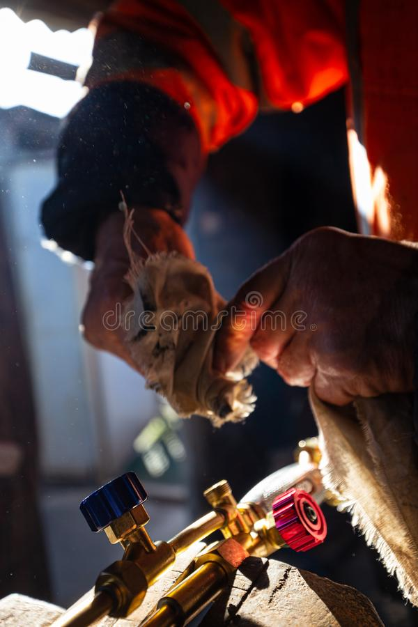 Torche de réparation et de nettoyage d'homme de coupe dans son atelier, foyer sélectif photographie stock