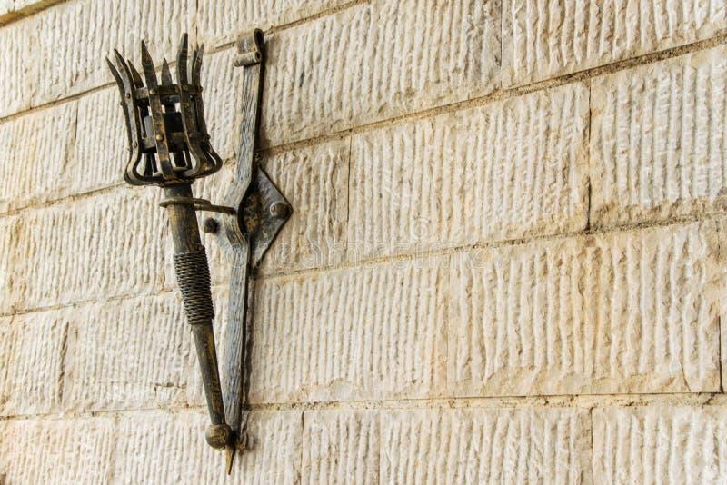 Torcia smontabile del ferro su una parete di pietra del castello medievale fotografie stock libere da diritti