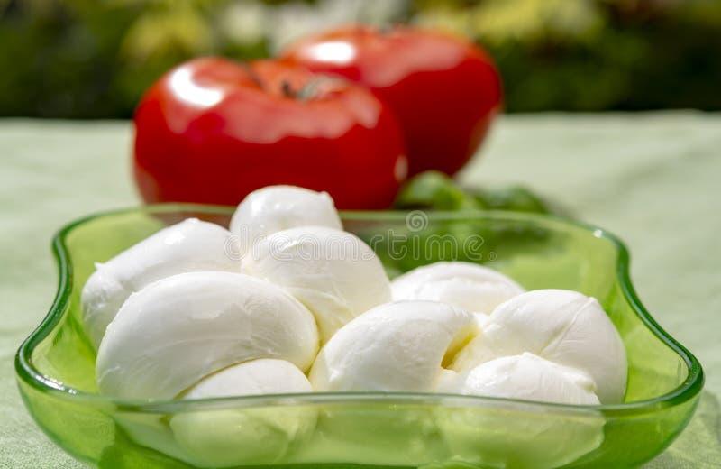 Tordu pour former un fromage ? p?te molle italien de mozzarella de treccia de tresse a servi avec le basilic et les tomates frais photos stock