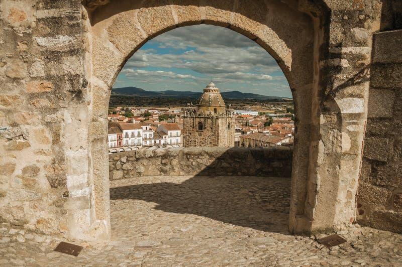 Toren met oude gebouwen die door overspannen steengateway in Trujillo worden gezien royalty-vrije stock foto