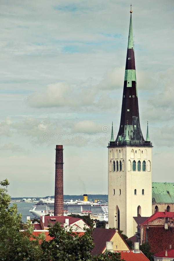 Toren Oleviste in de oude stad van Tallinn tegen de hemel en de veerboot op de achtergrond stock afbeeldingen