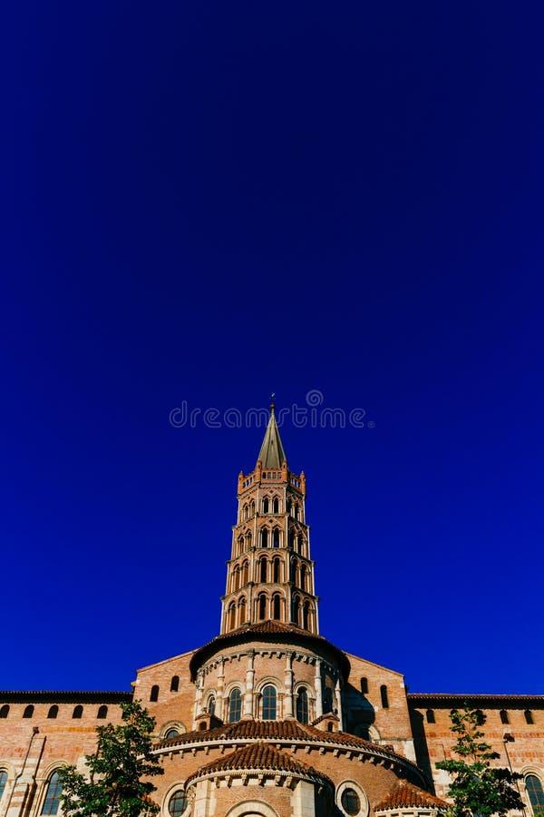 Toren van Basiliek van heilige-Sernin tegen blauwe hemel, in oude stad van Toulouse, Frankrijk royalty-vrije stock fotografie