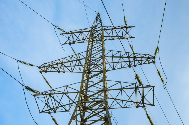 Toren van de lijnen van de hoogspanningsmacht tegen de blauwe hemel close-up Elektriciteitstransmissie stock afbeeldingen
