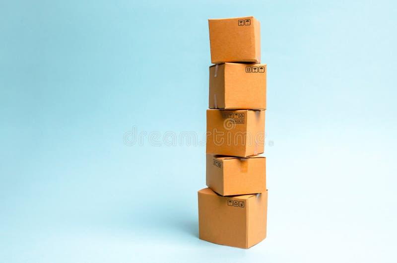 Toren van kartondozen op een blauwe achtergrond Het concept zich het bewegen en levering van goederen en goederen Handel en zaken stock foto